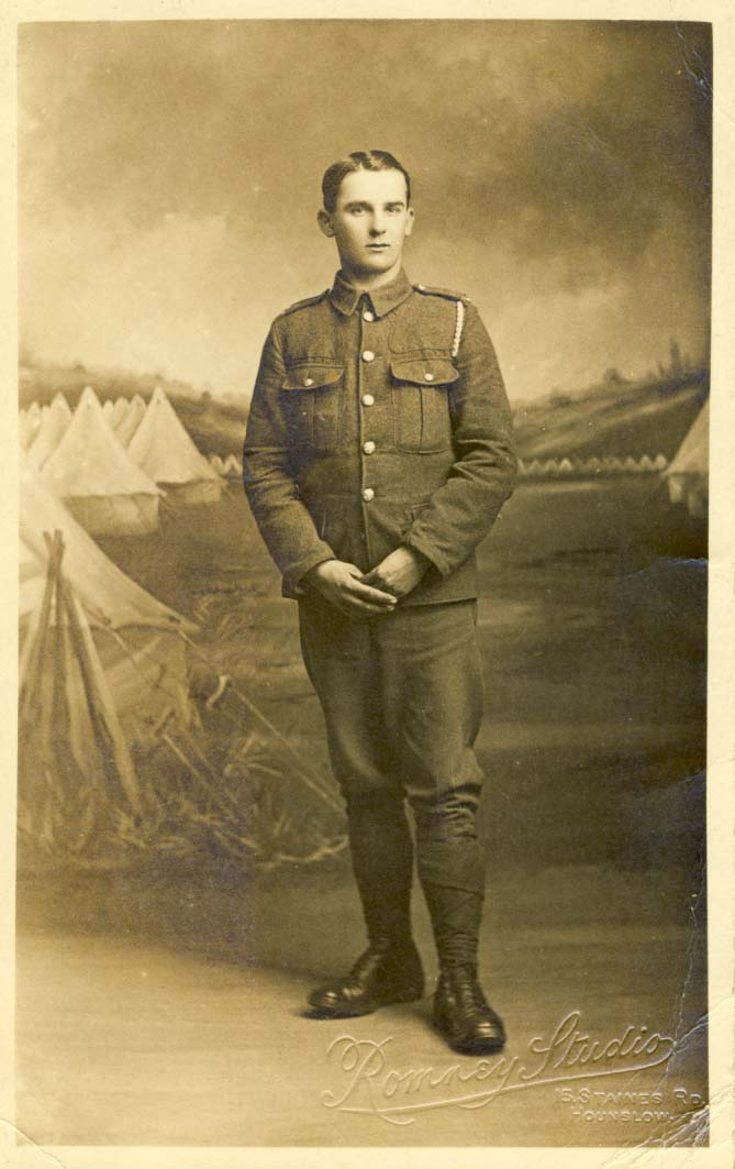 Infantry man, with hands crossed, standing in front of false backdrop of tents postcard