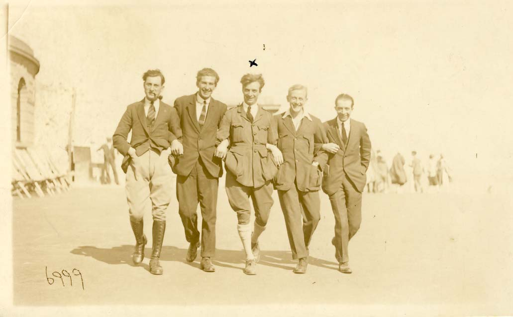 Five men, arm-in-arm, walking on a beach photograph