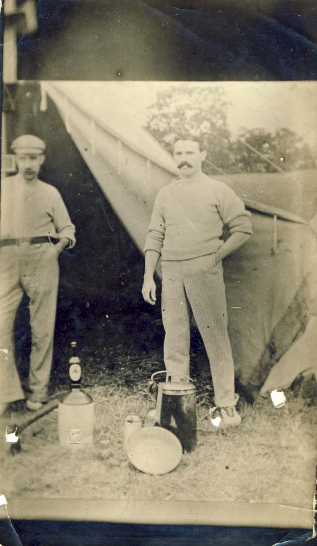 Harry in front of tent, bottle of beer on jug photograph