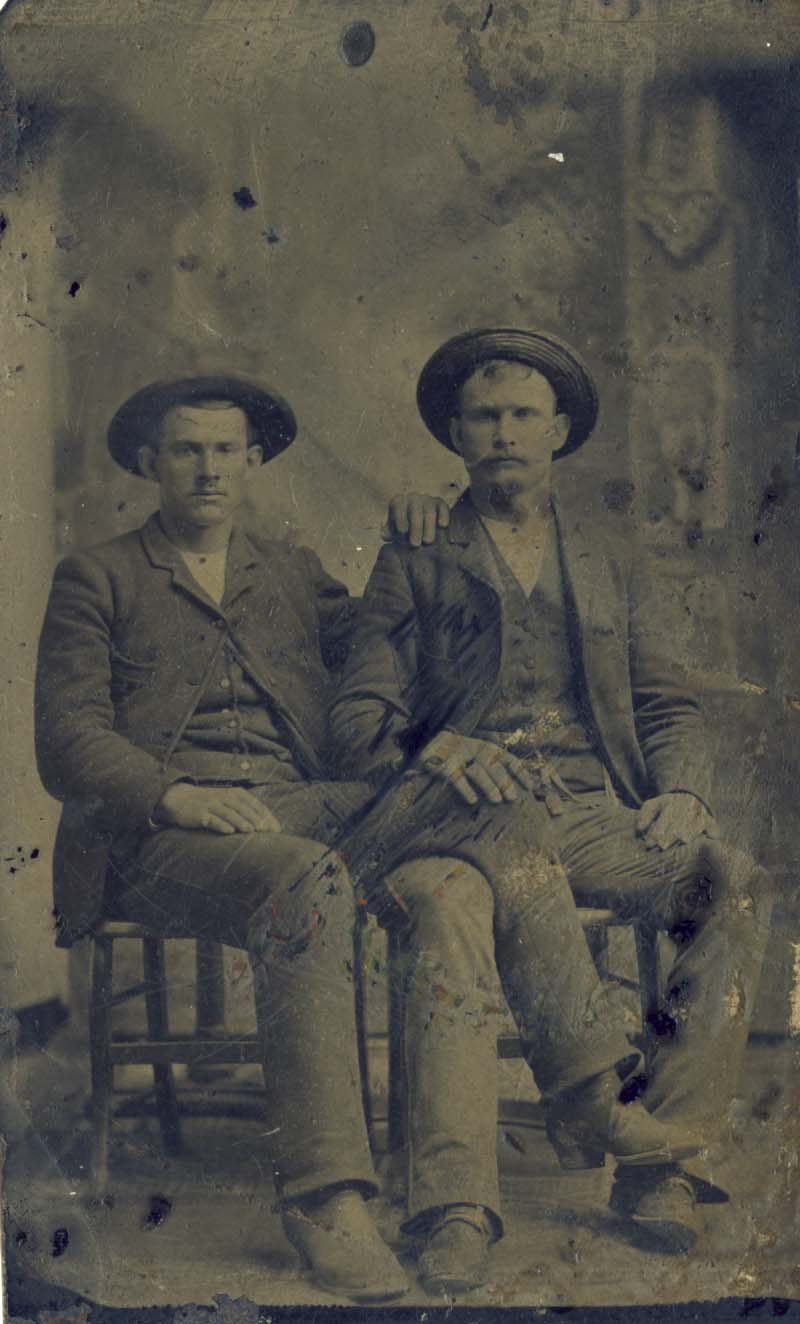 2 men seated, with hats, one with leg over the other tintype