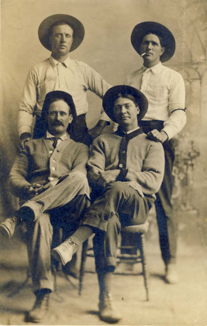 4 men wearing hats, two in sweaters photograph