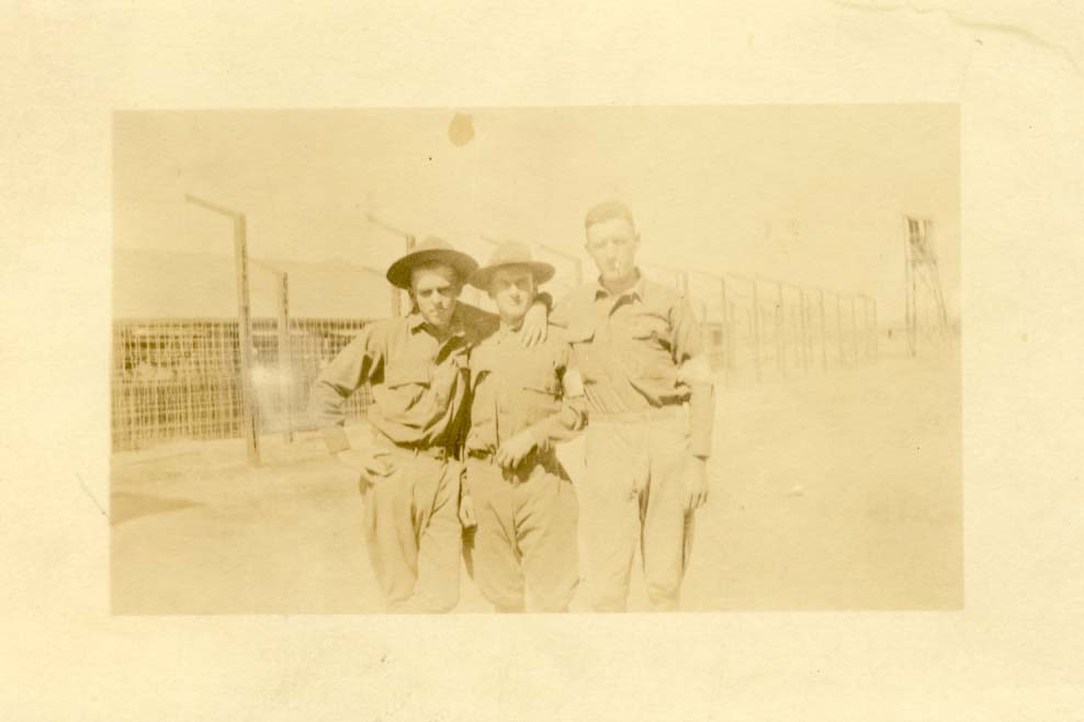 3 military men standing in front of camp surrounded by barbwire photograph
